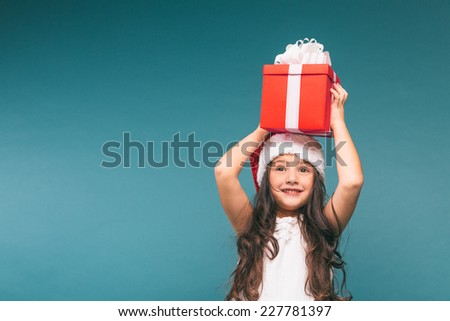 Smiling funny child (kid, girl) in Santa red hat. Holding Christmas gift in hand. Christmas concept. Shooting on blue background - stock photo