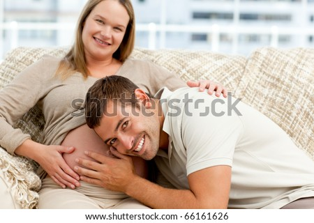 Smiling future dad listening to the belly of his wife sitting on the sofa in the living room - stock photo