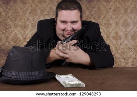 Smiling gangster holding handgun, close up. - stock photo