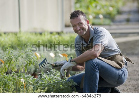 Smiling gardener in a greenhouse - stock photo