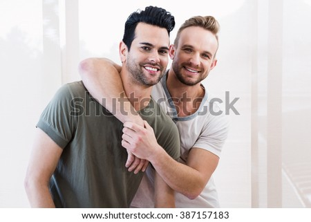 Smiling gay couple hugging at home - stock photo