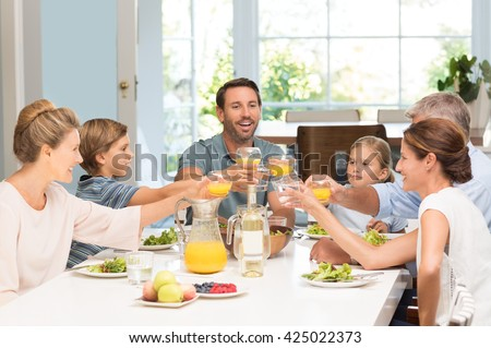 Smiling generation family raising glasses together in the kitchen. Happy parents with children and grandparents celebrating with a toast. Cheerful family raising toast with juice at dining table. - stock photo