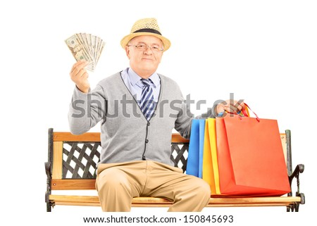 Smiling gentleman sitting on a wooden bench with shopping bags and holding US dollars isolated on white background - stock photo