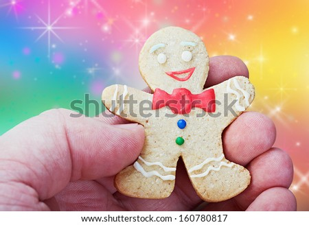 smiling gingerbread man in a hand on a background color - stock photo