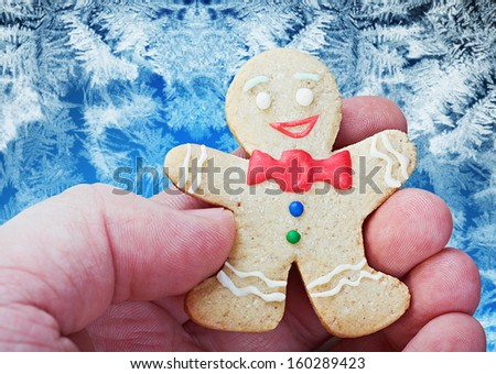smiling gingerbread man in the hand against frost - stock photo