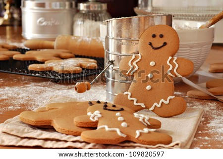 Smiling gingerbread man standing next to flour sifter with baking ingredients and additional gingerbread cookies in background.  Partially decorated cookies in foreground.  Closeup with shallow dof. - stock photo