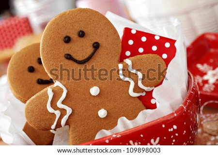Smiling gingerbread men nestled in holiday dish with gift-wrapped surprise.  Baking ingredients and supplies (including baker's twine and rolling pin) in background.  Macro with extremely shallow dof. - stock photo