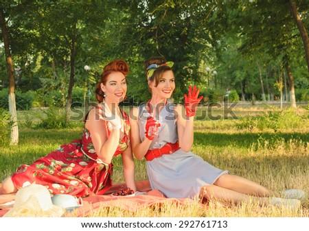Smiling girl at a picnic waving retro - stock photo