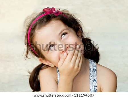Smiling girl closing her mouth with her hand - stock photo