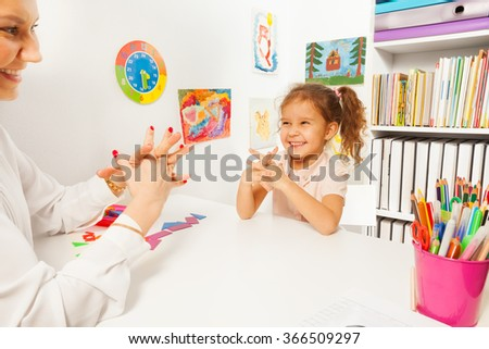 Smiling girl doing finger exercises as her teacher - stock photo