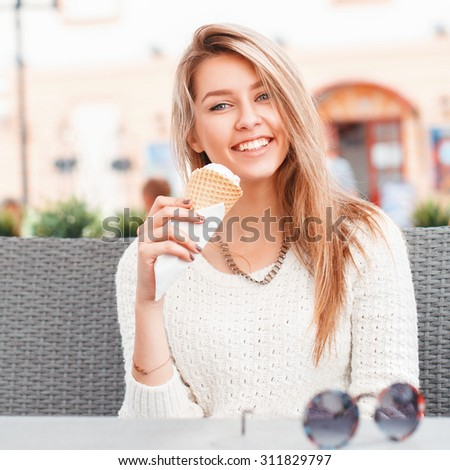 Smiling girl eating an ice-cream scoop in a waffle cone - stock photo
