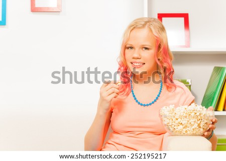 Smiling girl holding bowl with popcorn at home - stock photo