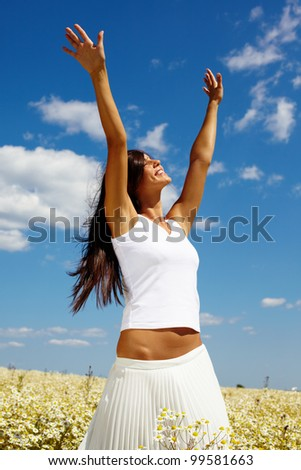 Smiling girl holding hands up in joy - stock photo