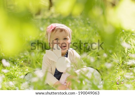smiling girl holding her rabbit toy - stock photo