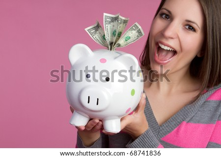 Smiling girl holding piggy bank - stock photo