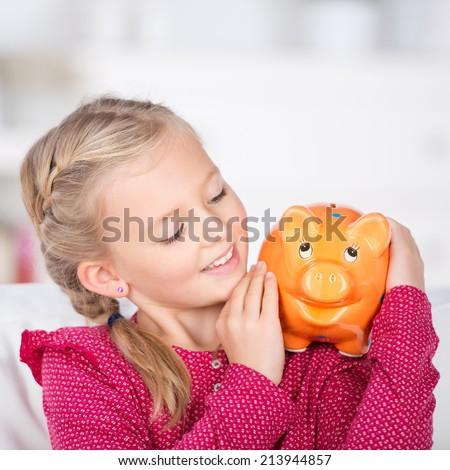 smiling girl holding piggy bank on her shoulder - stock photo