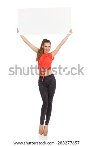 Smiling Girl Holds Up A Poster. Smiling young woman standing and holding blank placard above her head. Full length studio shot isolated on white. - stock photo