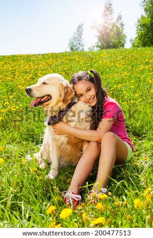 Smiling girl hugs cute dog sitting on the grass - stock photo