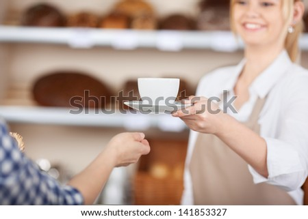 smiling girl in a coffeehouse passing a cup of coffee to a costumer - stock photo