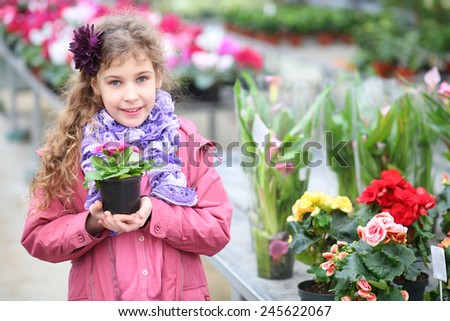 Smiling girl in a pink jacket holding flower pot in the hothouse - stock photo