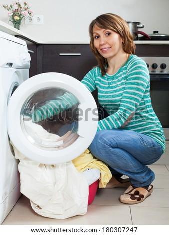 Smiling girl in green using washing machine at home - stock photo