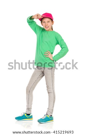 Smiling girl in pink full cap, green blouse, jeans and sneakers posing with hand on hip. Full length studio shot isolated on white. - stock photo