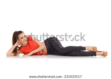 Smiling girl in red top, black jeans and high heels lying on the floor. Full length studio shot isolated on white. - stock photo