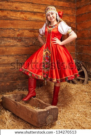 Smiling girl in Russian costume touching her hair - stock photo