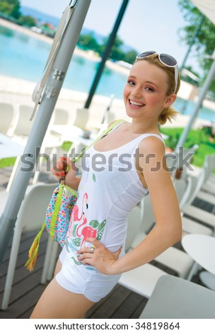 smiling girl in white summer clothes with bag - stock photo