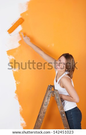 Smiling girl is painting her wall wit a roller - stock photo