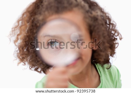Smiling girl looking through a magnifying glass against a white background - stock photo