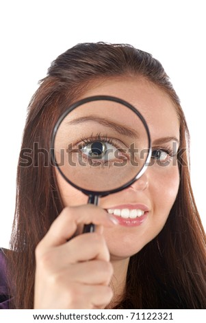 Smiling girl looking through magnifying glass - stock photo