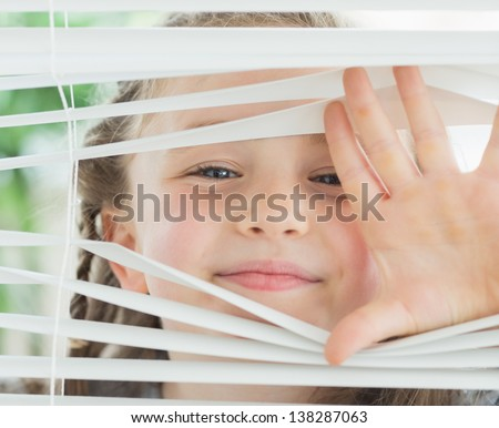 Smiling girl looking through the white window blinds - stock photo