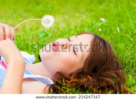 Smiling girl lying on grass and holding a dandelion - stock photo