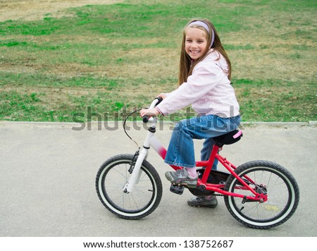Smiling girl on a bicycle in summer park outdoors - stock photo