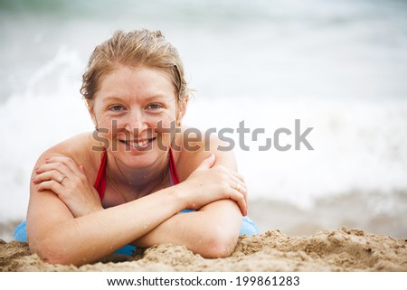 Smiling girl on the beach to sunbathe on the background of the surf (happiness on holiday) - stock photo