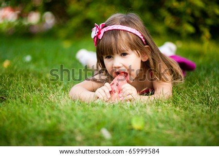 Smiling girl on the meadow eating watermelon - stock photo