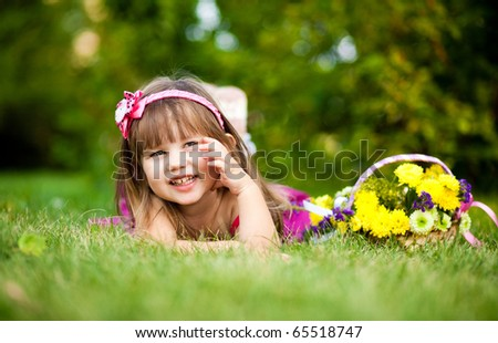 Smiling girl on the meadow looking right at camera - stock photo