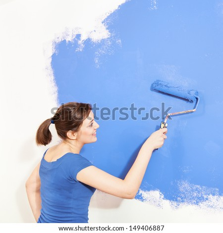 Smiling girl painting wall with blue paint - stock photo