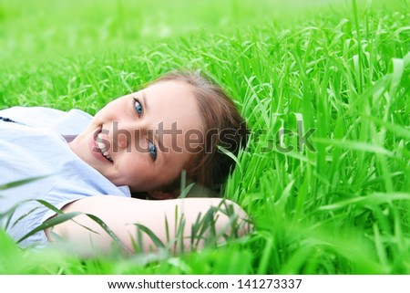 Smiling girl portrait, lying in grass field. Outdoor. - stock photo