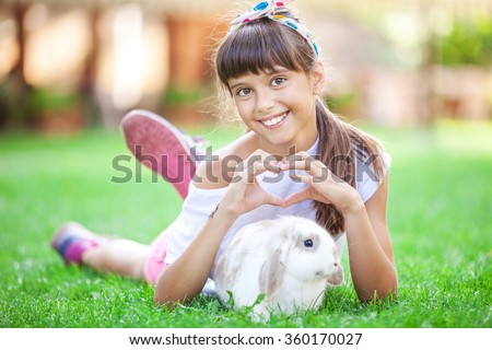 Smiling girl showing a heart sign with her hands over a pet rabbit - stock photo