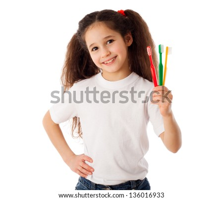 Smiling girl showing three toothbrushes, isolated on white - stock photo
