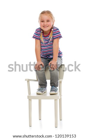 Smiling girl sitting on a chair. Studio shot. - stock photo