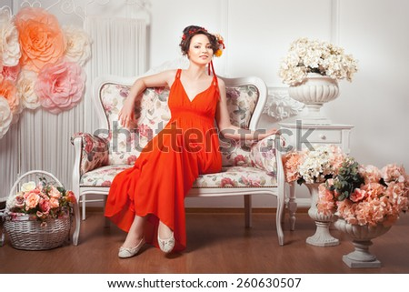 Smiling girl sitting on a couch in a red dress, flowers in her hair. - stock photo