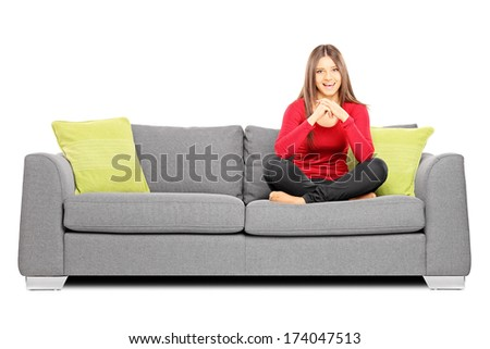 Smiling girl sitting on a sofa and looking at camera isolated on white background - stock photo