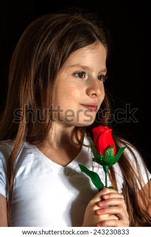 smiling girl smells a red rose on black background - stock photo