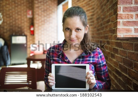 Smiling girl spending time in a cafe using digital tablet - stock photo