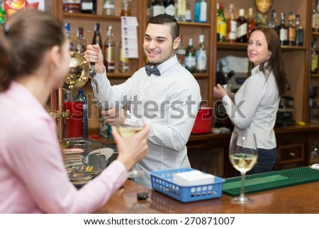 Smiling girl standing at bar with glass of wine and flirting with barman. Focus on guy - stock photo
