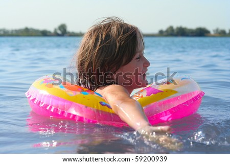smiling girl swimming on a lake - stock photo