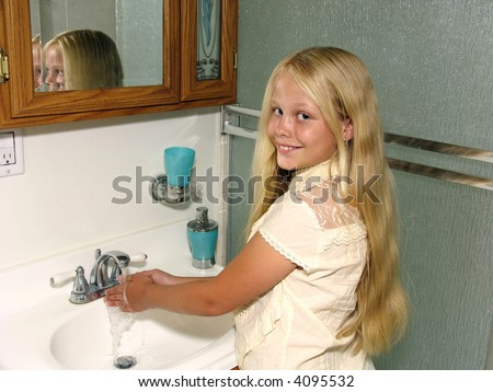 Smiling girl washing her hands in a bathroom sink - stock photo